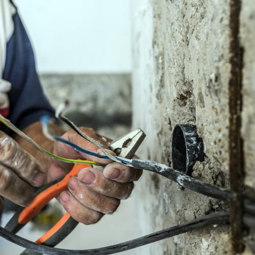 Photo of Electrician peeling off insulation from wires - closeup on hands and pliers. electrician binding copper wires together and sealing them with insulation stripe. Man mounting the wires into electrical wall fixture or socket - closeup on hands and pliers.